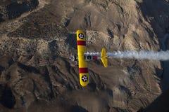 Biplan jaune au-dessus de désert Photographie stock