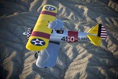 Biplan jaune au-dessus de désert Images libres de droits