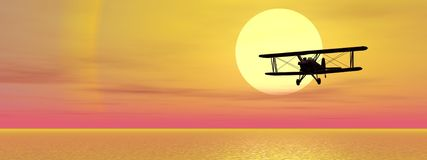 Biplan upon ocean. Old biplan flying upon ocean by sunset Royalty Free Stock Image