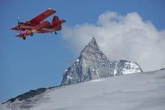 Biplan rouge au-dessus du Matterhorn Photos libres de droits