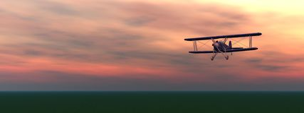 Biplan by sunset. Old biplan flyinig upon the ground by colorful cloudy sunset Stock Image
