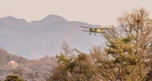 Biplan volant au-dessus de la région montagneuse Photographie stock libre de droits