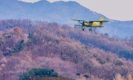 Biplan volant au-dessus de la région montagneuse Images libres de droits