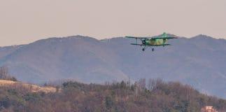 Biplan volant au-dessus de la région montagneuse Image stock