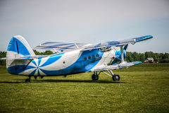 Biplane. Blue and white biplane parked on a grass field Royalty Free Stock Images
