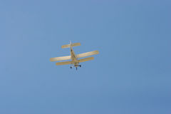 Biplane flying in the blue sky Stock Photography