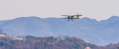 Biplane flying over mountainous region. Chungju, South Korea, February 22, 2018: ROK military biplane training aircraft flying over mountainous region on Stock Photography