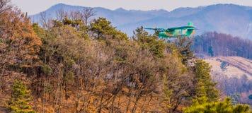 Biplane flying over mountainous region. Chungju, South Korea, February 22, 2018: ROK military biplane training aircraft flying over mountainous region on Stock Images