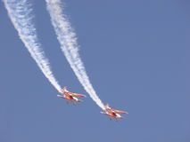 Biplane formation. Two biplanes trailing show smoke fly in a clear blue sky stock image