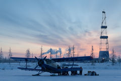 Biplane next to oil derrick on winter sunrise background Stock Image