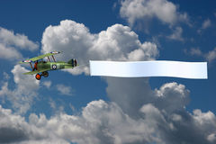 Biplane Pulling a Blank Banner. 3D render of a biplane pulling a blank banner. The background is one of my sky photographs Stock Photos