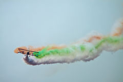 Biplane smoking out Indian Flag in blue sky Royalty Free Stock Image