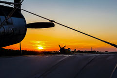Biplane standing at sunset. Double winged propeller silhouetted against a golden sunrise sunset royalty free stock photography