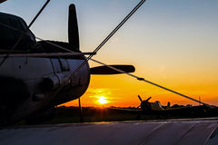 Biplane standing at sunset. Double winged propeller silhouetted against a golden sunrise sunset Stock Images