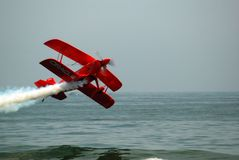 Biplane Stunts over the water. A red bi-plane flies extremely close to the ocean surface during an air show stock photography