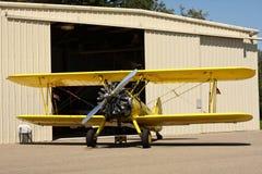 Biplano amarillo delante del hangar Imagen de archivo libre de regalías