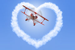Biplano che crea una forma del cuore nel cielo Fotografia Stock Libera da Diritti