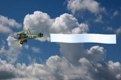 Biplano que tira de una bandera en blanco Fotos de archivo