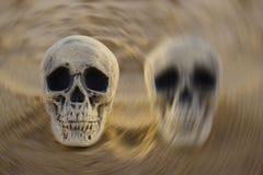 Bipolair wanordeconcept: twee schedels op zand stock foto's