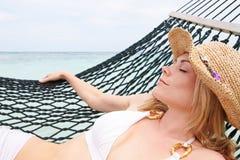 Biquini da mulher e chapéu vestindo de Sun que relaxa na rede da praia Imagens de Stock