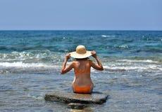 Biquini 'sexy' que bronzea-se a mulher que relaxa na praia com um chapéu Fotos de Stock