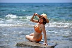 Biquini 'sexy' que bronzea-se a mulher que relaxa na praia com um chapéu Foto de Stock