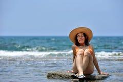 Biquini 'sexy' que bronzea-se a mulher que relaxa na praia com um chapéu Imagem de Stock