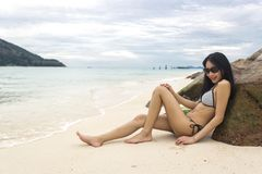 Biquini vestindo da mulher asiática magro nova que encontra-se em rochas do mar, em mar e em ondas como o fundo foto de stock royalty free
