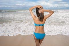 Biquini vestindo da mulher 'sexy' bonita nova e relaxamento no Sandy Beach branco perto das ondas do azul na praia tropical fotografia de stock