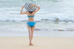 Biquini vestindo da mulher 'sexy' bonita nova e relaxamento no Sandy Beach branco perto das ondas do azul na praia tropical imagem de stock