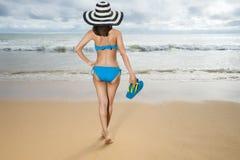 Biquini vestindo da mulher 'sexy' bonita nova e relaxamento no Sandy Beach branco perto das ondas do azul na praia tropical imagens de stock royalty free