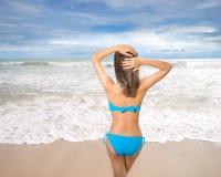Biquini vestindo da mulher 'sexy' bonita nova e relaxamento no Sandy Beach branco perto das ondas do azul na praia tropical fotos de stock