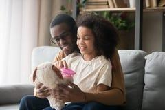 Biracial дочь сидя на подоле папы расчесывая заполненную собаку игрушки стоковое изображение