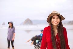 Biracial предназначенная для подростков девушка в красных платье и шляпе на пляже стоковое фото rf