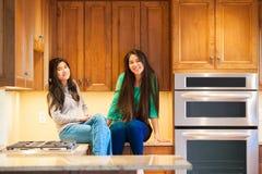 2 biracial предназначенных для подростков девушки сидя на toget счетчика кухни усмехаясь Стоковые Фотографии RF