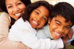 Biracial семья смеясь над и усмехаясь снаружи стоковое фото