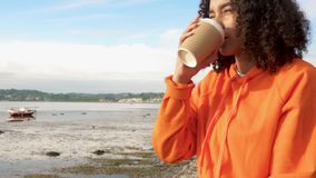 Biracial African American girl teenager on a sea front using her smart watch for social media and drinking coffee. Beautiful mixed race African American girl stock footage