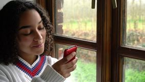 Biracial African American girl teenager young woman using her mobile cell phone or smartphone for social media. Happy smiling beautiful mixed race African stock video footage