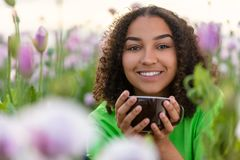 Biracial Afroamerikaner-Jugendlich-Frauen-trinkender Kaffee in den Blumen stockbilder