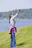 Biracial asian girl flying kite by  lake Royalty Free Stock Image