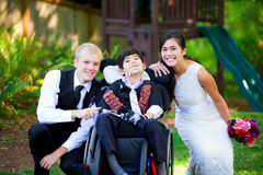 Biracial bride and groom with her little disabled brother in whe Royalty Free Stock Image