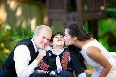 Biracial bride kissing her little brother on her wedding day. Ch Stock Photos