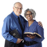 Biracial Couple with Bibles. A mixed race senior couple happily holding their Bibles. On a white background royalty free stock photos