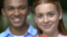 Biracial couple smiling together, showing paper heart into camera, romance. Stock footage stock video footage