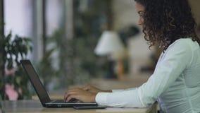 Biracial damy pisać na maszynie email na laptopie przy biurem, używać komputer dla komunikaci zbiory