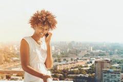 Biracial dziewczyna na balcomy drapacz chmur z smartphone Obrazy Stock