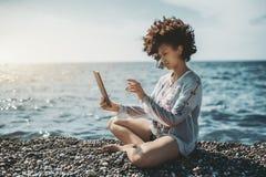 Biracial dziewczyna na seashore z cyfrową pastylką Obrazy Royalty Free
