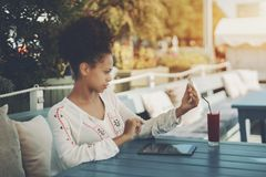 Biracial dziewczyna w ulica barze z smartphone i cyfrowym ochraniaczem Fotografia Royalty Free