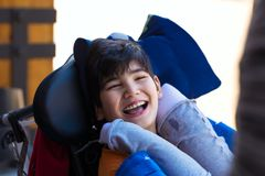 Biracial eleven year old boy in wheelchair outdoors, smiling. Biracial Asian Caucasian disabled boy in wheelchair smiling outdoors. He has cerebral palsy royalty free stock photography