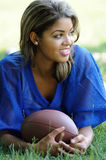 Biracial female football player 1. Pretty female biracial football player in blue mesh jersey laying in grass - looking off frame royalty free stock image